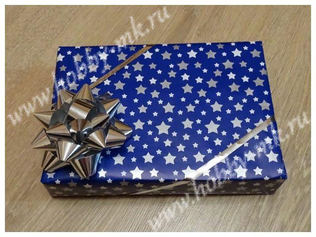 Прямоугольная коробка с подарком, упакованная в подарочную бумагу